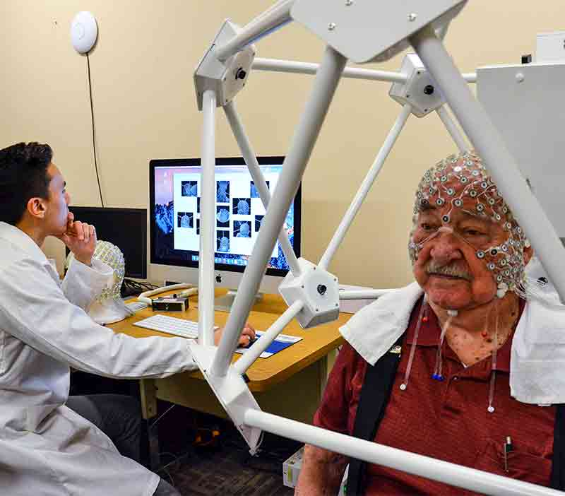 Image of senior male wearing Dense Array EEG sensor net, with lab technician in background.